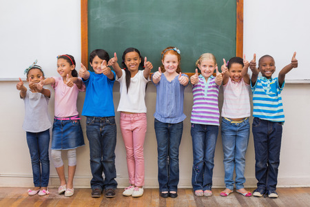 Photo for Cute pupils smiling at camera in classroom at the elementary school - Royalty Free Image