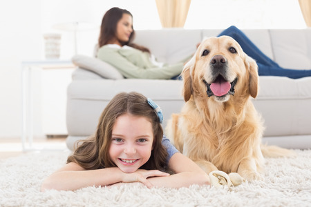 Portrait of happy girl with dog lying on rug while mother relaxing at homeの写真素材