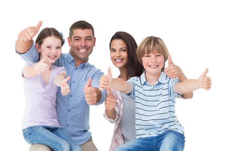 Foto de Portrait of happy family gesturing thumbs up over white background - Imagen libre de derechos