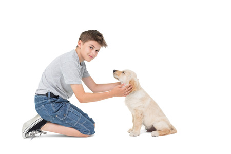 Full length portrait of boy stroking dog while kneeling over white background