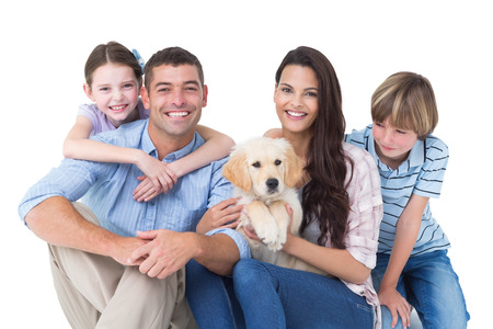 Portrait of happy family with cute dog over white background
