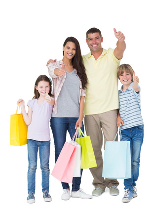 Photo pour Portrait of happy family with shopping bags gesturing thumbs up over white background - image libre de droit
