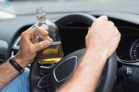 Man drinking alcohol while driving in his car