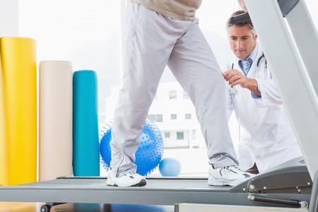 Senior man on treadmill with therapist crouching in fitness studio