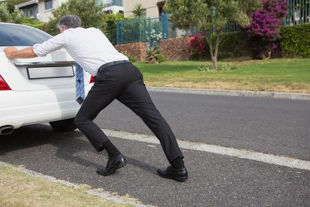 Man pushing his broken down car on the road