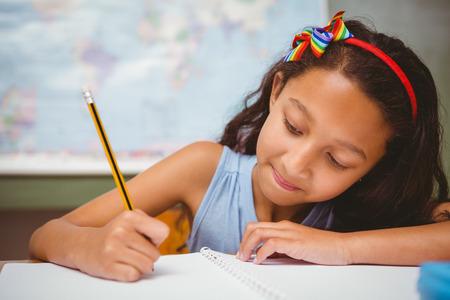 Photo pour Portrait of cute little girl writing book in classroom - image libre de droit