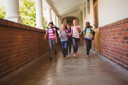 Full length portrait of school kids running in school corridor