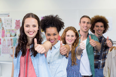 Portrait of confident and attractive fashion designers gesturing thumbs up