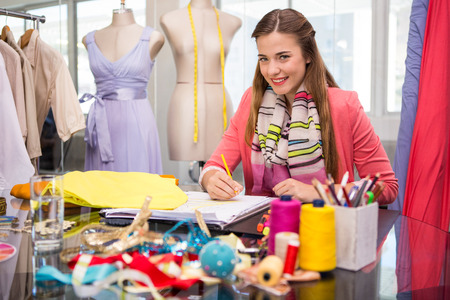 Foto de Portrait of attractive female fashion designer sketching at table - Imagen libre de derechos