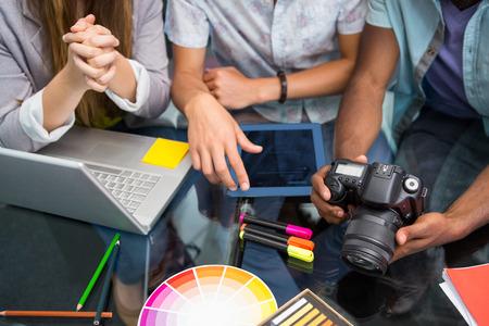 Photo pour Close up of creative business people with digital camera at office desk - image libre de droit
