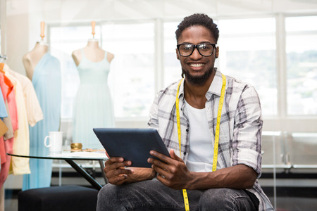 Foto per Portrait of smiling confident male fashion designer with digital tablet - Immagine Royalty Free