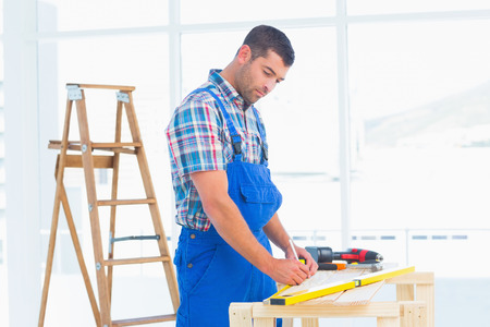 Handyman working at workbench in bright office