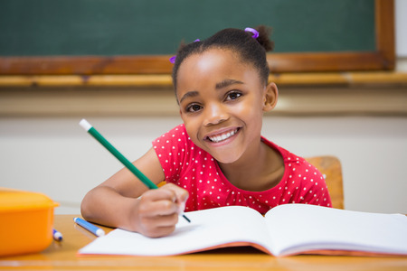 Photo pour Cute pupils writing at desk in classroom at the elementary school - image libre de droit