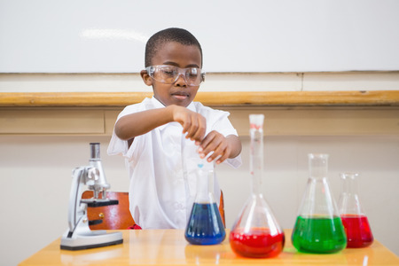 Cute pupil looking at liquids at elementary school