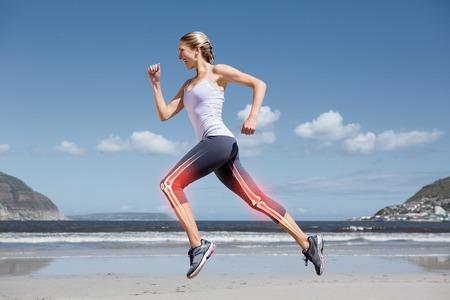 Foto de Digital composite of Highlighted leg bones of jogging woman on beach - Imagen libre de derechos