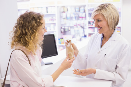 Pharmacist giving medicine to costumer at pharmacy