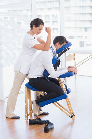 Businessman having back massage in medical office