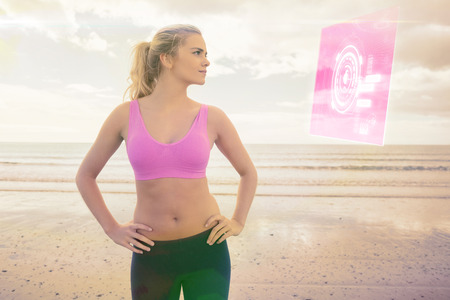 Toned woman with hands on hips on beach against fitness interface