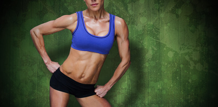 Female bodybuilder against green paint splashed surface