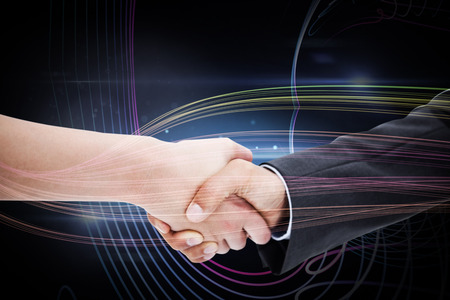 Close up of a handshake against black background with spark