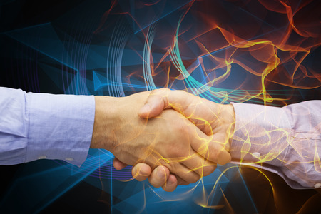 Hand shake in front of wires against futuristic glowing lines on black background