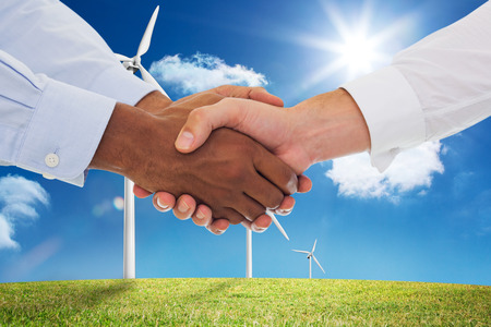 Close-up shot of a handshake in office against digital landscape with three wind turbines