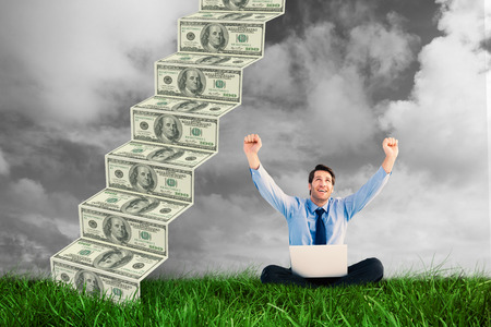 Businessman cheering with laptop sitting on floor against green grass under grey sky