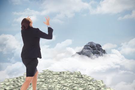 Businesswoman gesturing against mountain peak through the clouds