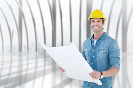 Happy architect holding blueprint in house against white room with large window overlooking city