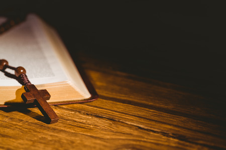 Open bible with rosary beads on wooden table