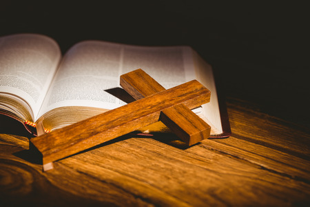 Open bible with crucifix icon on wooden table