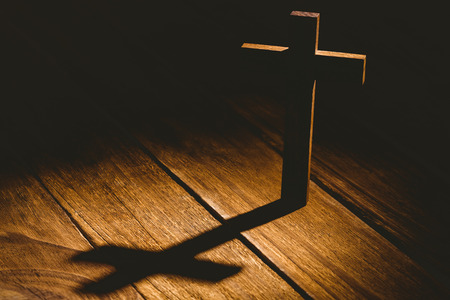 Crucifix icon on wooden table in the shadow
