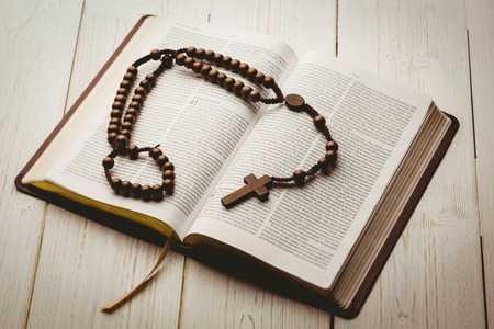Open bible and wooden rosary beads on wooden table