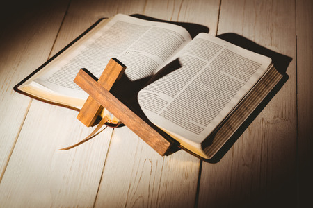 Open bible and wooden cross on wooden table