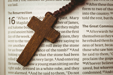 Open bible and wooden cross overhead shot
