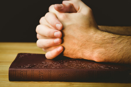 Man praying over his bible on wooden table