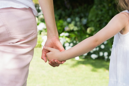 Mother and daughter holding hands outside in the garden