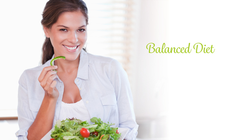 The word balanced diet against smiling woman eating a salad