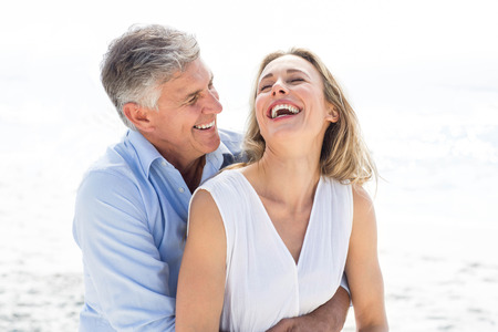 Photo pour Happy couple laughing together at the beach - image libre de droit