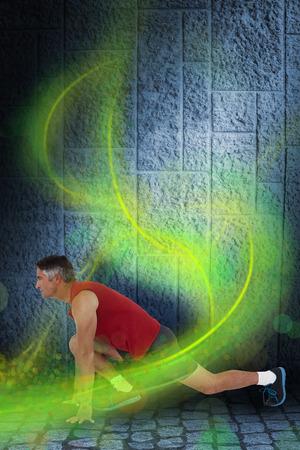 Foto de Fit man stretching his legs against dark grey room - Imagen libre de derechos