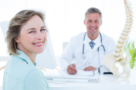 Patient and doctor smiling at camera in medical office
