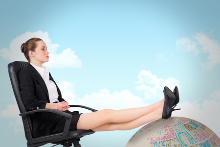 Businesswoman sitting on swivel chair with feet up against blue sky