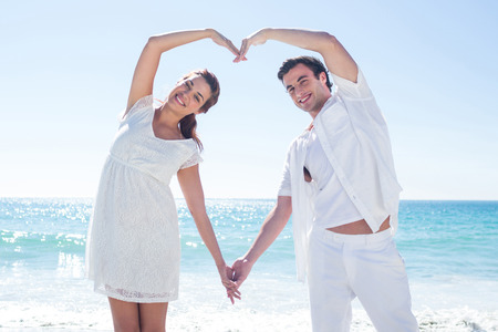 Happy couple forming heart shape with their hands at the beachの写真素材