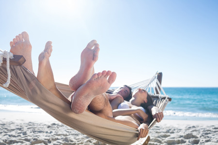 Photo pour Happy couple napping together in the hammock at the beach - image libre de droit