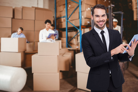 Businessman using his tablet while looking at the camera  against people at work in warehouse