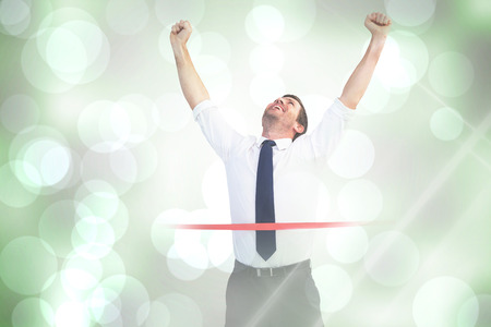 Businessman celebrating success with arms up against grey abstract light spot design
