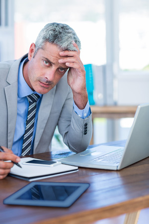 Depressed businessman trying to work in office