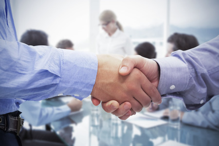 Photo for Two men shaking hands against business people in board room meeting - Royalty Free Image