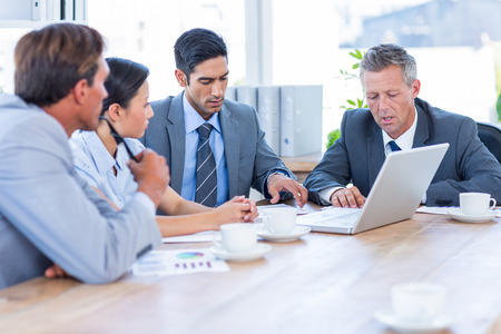 Business people speaking together during meeting in office