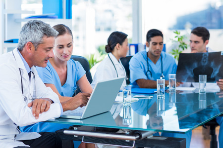 Photo for Doctor and nurse looking at laptop with colleagues behind in medical office - Royalty Free Image
